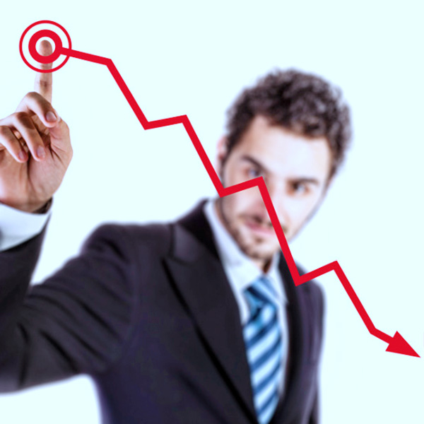 a young and handsome businessman touching a descending red financial graph. PhotoDune.