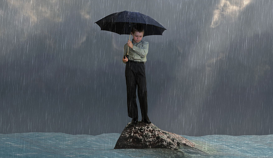 man standing on a rock holding an umbrella in the flood