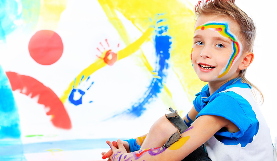 creative boy playing with paint