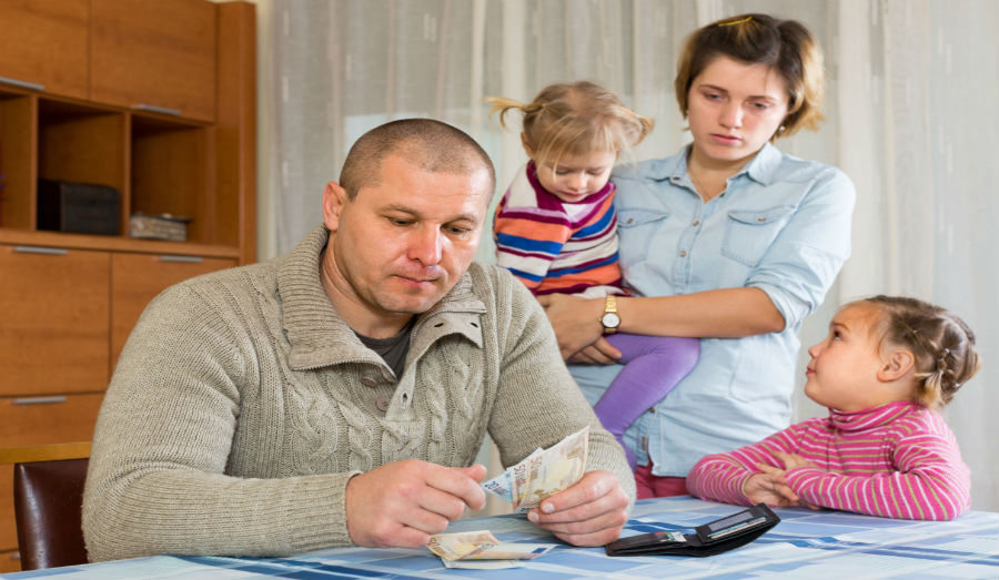 family sitting around table sad counting money