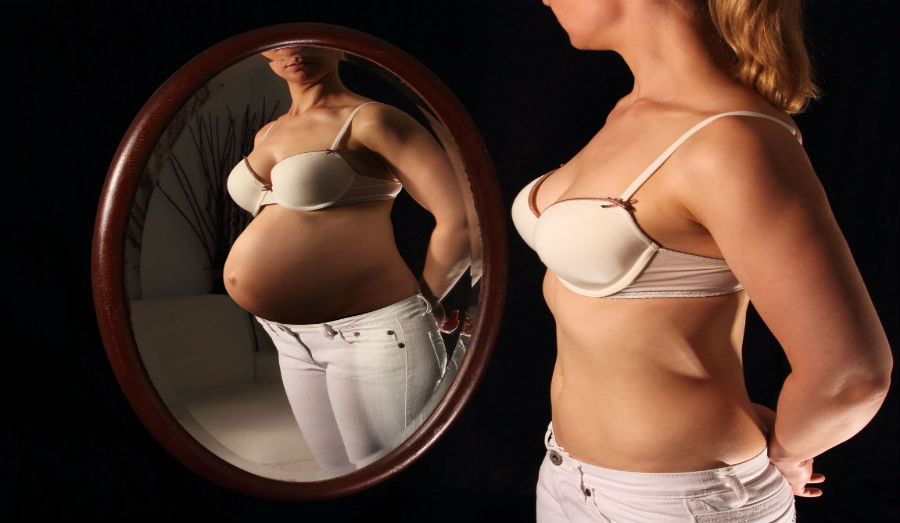 Woman seeing herself pregnant in the mirror