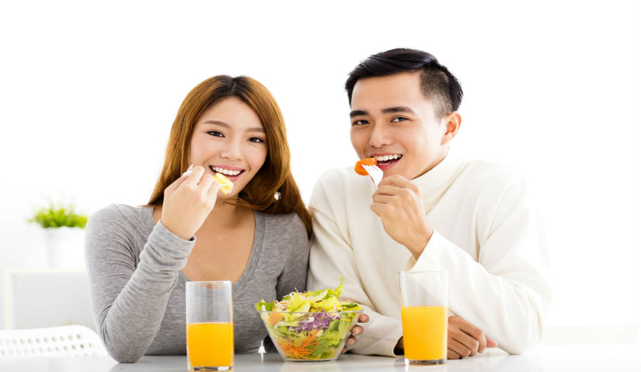 Couple eating a salad and drinking orange juice