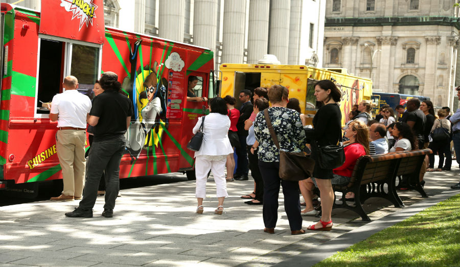 People waiting for their lunch at food trucks into the business area in Montreal, Quebec on july 23.