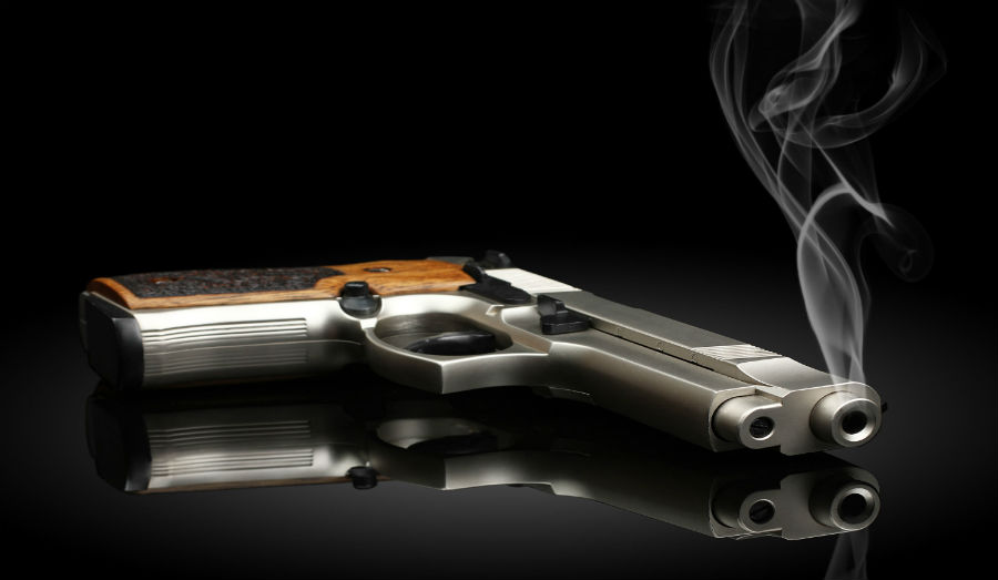 Chromed handgun on black background with smoke