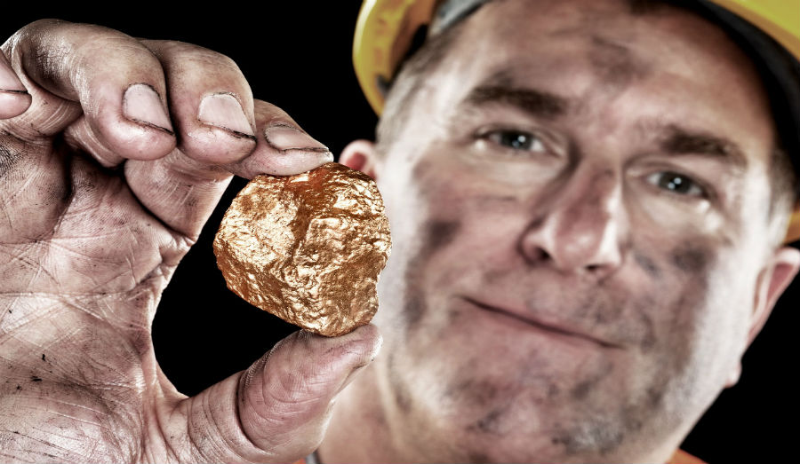 Miner holding a nugget of gold