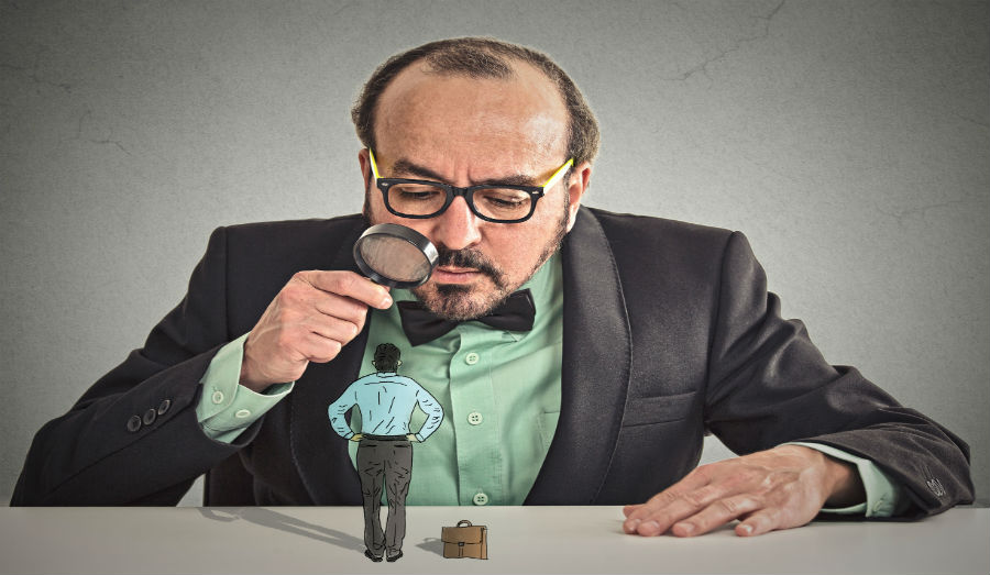 Curious corporate businessman skeptically meeting looking at small employee standing on table through magnifying glass isolated office grey wall background.